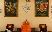 Swamiji sitting on the stage in the meditation hall
