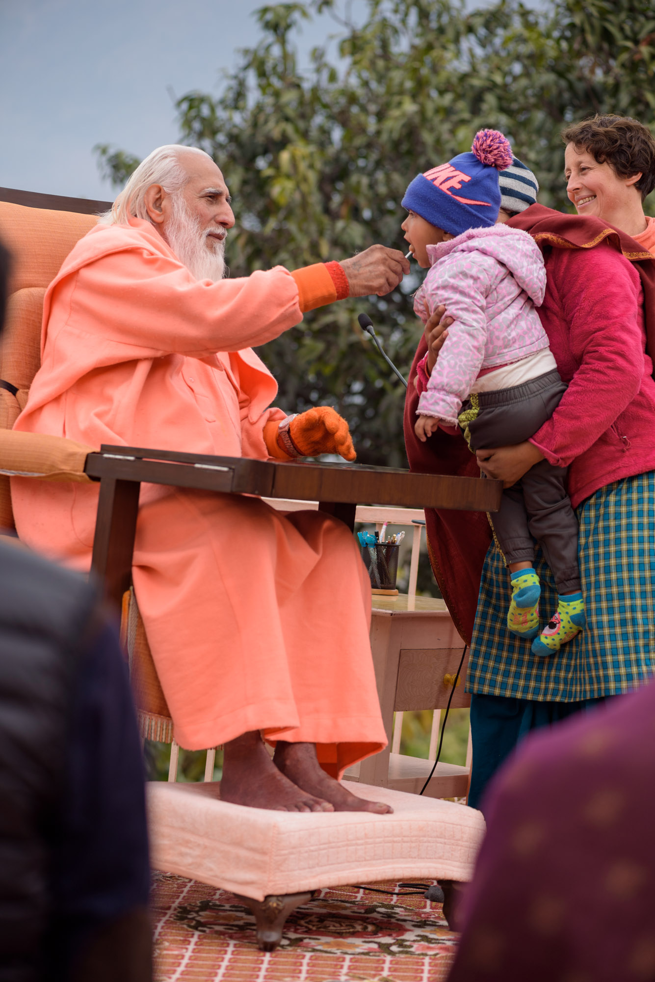 Swamiji feeding a lollipop to a child
